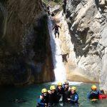 Une fine équipe pose pendant qu'un canyoneur saute le grand toboggan de la clue de la Maglia